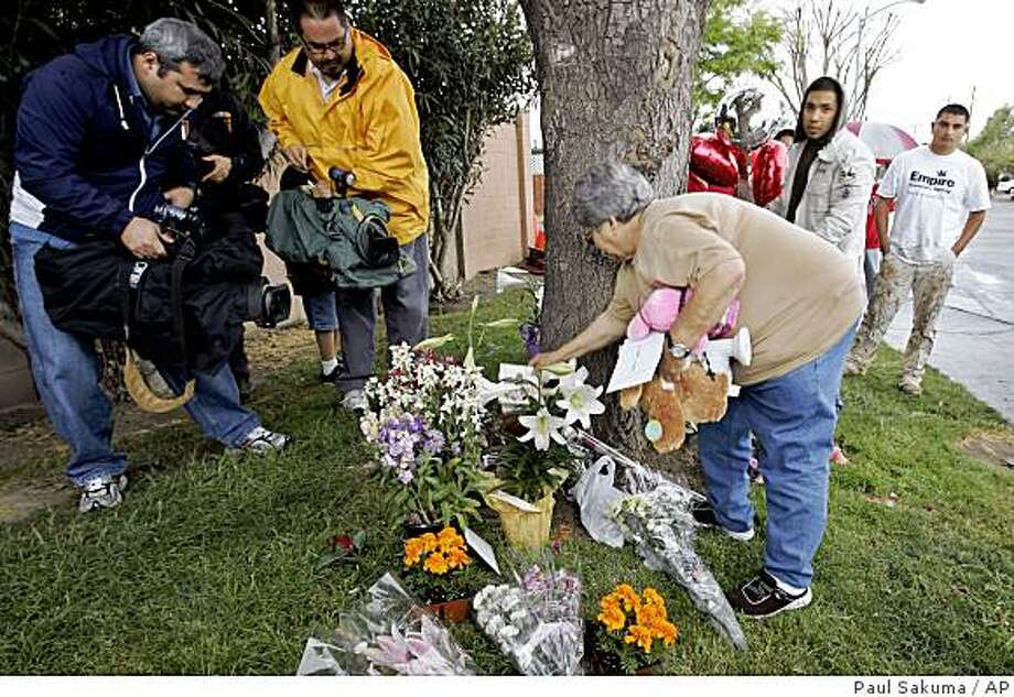 A woman pick up items to clean up the area at a memorial for Sandra Cantu in Tracy, Calif., Thursday, April 9, 2009, near the home of Cantu. The body of Cantu, 8, was discovered inside a suitcase in an irrigation pond on Monday, April 6, 2009 after she was last seen at her home on March 27, 2009. (AP Photo/Paul Sakuma) Photo: Paul Sakuma, AP