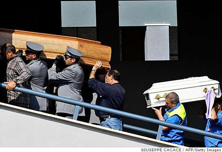 """Coffins of victims of the April 6 earthquake are carried inside the cemetery on April 10, 2009 following the ceremony in the vast square courtyard of a """"Guardia di Finanzia"""" police training centre in the Abruzzo capital L'Aquila. Italy marked a day of mourning today with a state funeral set for the nearly 300 dead in this week's devastating earthquake and as many survivors remained desperate for shelter. AFP PHOTO / GIUSEPPE CACACE (Photo credit should read GIUSEPPE CACACE/AFP/Getty Images) Photo: GIUSEPPE CACACE, AFP/Getty Images"""
