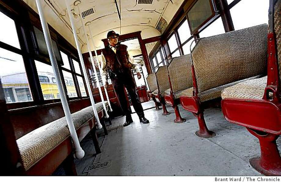 Gene Martin, who used to drive the old No. 1, walks through the passenger area with rattan covered seats. San Francisco's first publicly owned streetcar, which made its maiden run 97 years ago, will be restored at a cost of $1.8 million in time for MUNI's centennial celebration. Photo: Brant Ward, The Chronicle
