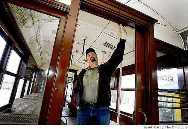 Karl Johnson, transit mechanic supervisor, looks up at the fine woodwork on the old streetcar. San Francisco's first publicly owned streetcar, which made its maiden run 97 years ago, will be restored at a cost of $1.8 million in time for MUNI's centennial celebration. Photo: Brant Ward, The Chronicle