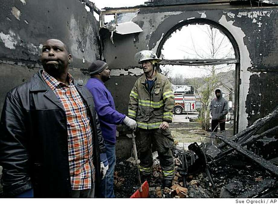 Nathan Christmon, left, surveys the damage to his home in Midwest City, Okla., Friday, April 10, 2009, as Midwest City firefighter Major Reese Morrison, right, tells him and his brother, Drew Christmon, center, that they must leave the home until it has been declared safe. Firefighters mopped up hot spots Friday from wind-driven wildfires in western and central Oklahoma that left at least 34 people injured and more than 100 homes or other structures damaged or destroyed. (AP Photo/Sue Ogrocki) Photo: Sue Ogrocki, AP