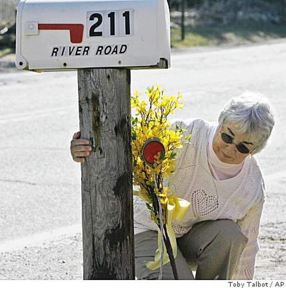 An unidentified woman places flowers on the mailbox at the home of Capt. Richard Phillips in Underhill, Vt., Friday, April 10, 2009.  Phillips, the American captain held hostage by four Somali pirates, made a desperate escape attempt Friday but was recaptured. (AP Photo/Toby Talbot) Photo: Toby Talbot, AP