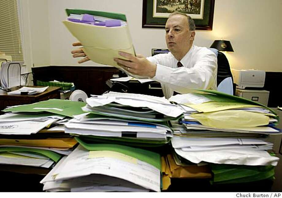 Attorney Bryan Elliott looks over bankruptcy files at his office in Hickory, N.C., on April 1, 2009.  More than three years after Congress made it much tougher to use bankruptcy to duck debt, bankruptcy courts are well on their way toward being as busy as ever, according to an Associated Press analysis. Photo: Chuck Burton, AP