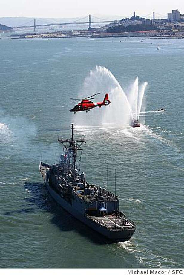 The USS Vandergrift, a frigate, cruises into San Francisco for Fleet Week. A Coast Guard helicopter buzzes overhead. Photo: Michael Macor, SFC