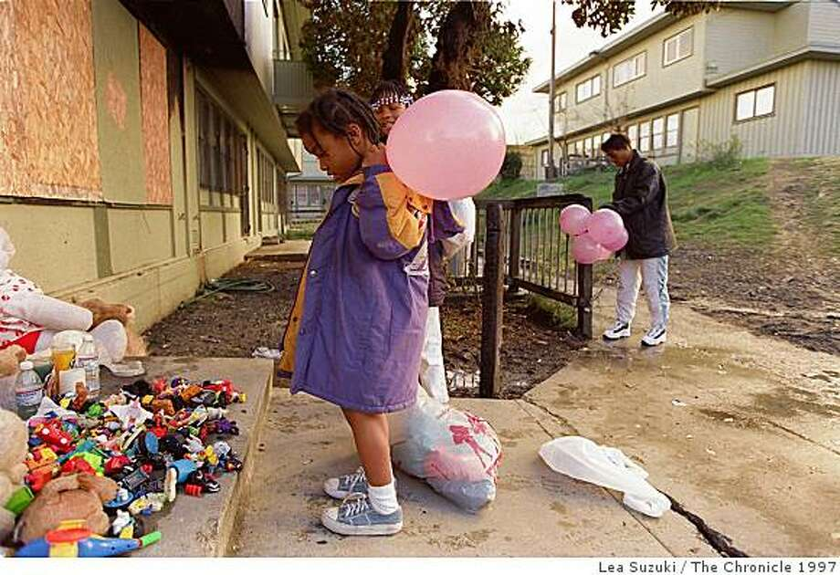 """Katrina Benjamin, 6; Kevina Moore, 9 (her head shows behind Katrina); and Pam Jackson, long time friend of Delores Evans. Benjamin looks over the memorial with her sister Kevina that is situated on the front steps of the home where 6 perished in a fire on Saturday as her mother Pam Jackson ties a bunch of pink ballons with the words, """"I LOVE YOU!"""" written on them to a fence. Photo By Lea Suzuki / THE CHRONICLE. 1997 Photo: Lea Suzuki, The Chronicle 1997"""