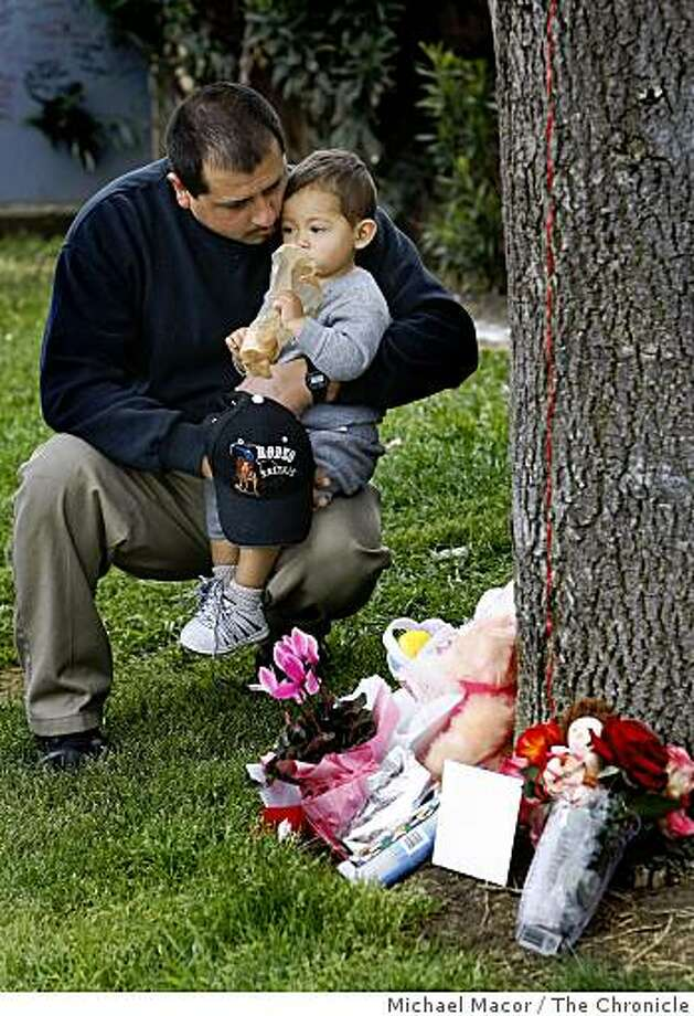 Artemie Pimentel of Tracy, holds his son Guadalupe, 3, at the memorial to Sandra Cantu, outside the trailer park where she was last seen. Photo: Michael Macor, The Chronicle