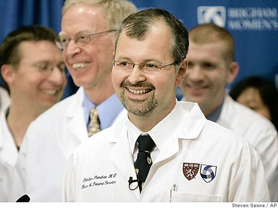 Plastic surgeon Dr. Bohdan Pomahac, center, smiles while facing reporters along with other medical staff, during a news conference at Brigham and Women's Hospital, in Boston, Friday, April 10, 2009. Pomahac led a surgical team that performed the nation's second partial face transplant on a man who suffered traumatic facial injuries from an accident. Chief, Division of Plastic Surgery, Dr. Elof Eriksson, appears center left. (AP Photo/Steven Senne) Photo: Steven Senne, AP