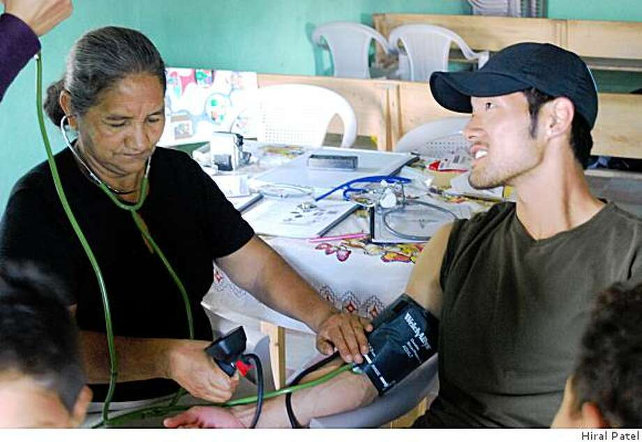 Reina Isabel Pineda, a woman from a rural community called Los Pajarillos, Honduras that was trained as community health worker (CHW), taking Hiral Patel's blood pressure. Photo: Hiral Patel