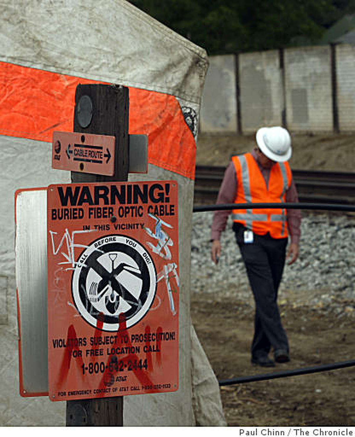 A sign warns that buried communications cables are present next to the underground vault where police suspect vandals entered and cut several of the lines in San Jose on Thursday.
