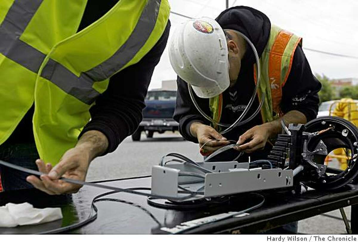 Bruce Bennett, left, and Jordan Bechetl, right, of Golden State Utility, prep cable before applying a fusion splice as they work to repair a fiber-optic cable that was cut by vandals in San Carlos, Calif., on Thursday, April 9, 2009.