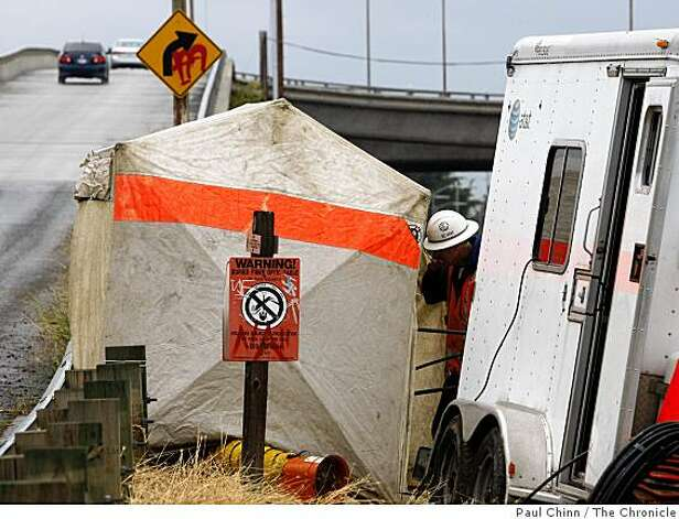 An AT&T technician enters a tent covering an underground vault where fiber-optic communication cables were severed off Monterey Highway in San Jose on Thursday. Photo: Paul Chinn, The Chronicle