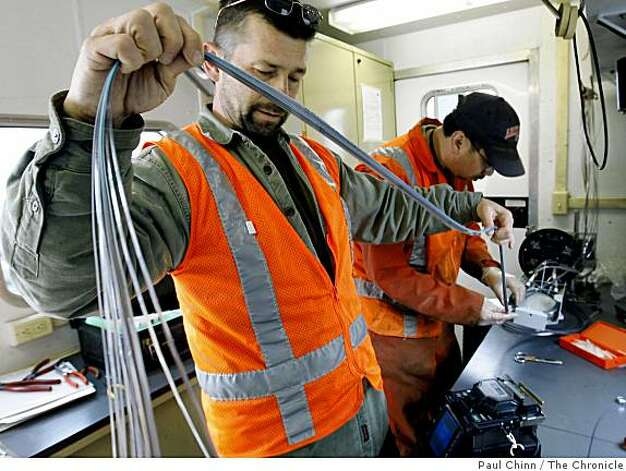AT&T technicians Herb Neumann (left) and Bonnard Gallo reconnect dozens of fiber-optic communications cables that were severed in the early morning hours in San Jose on Thursday. Photo: Paul Chinn, The Chronicle