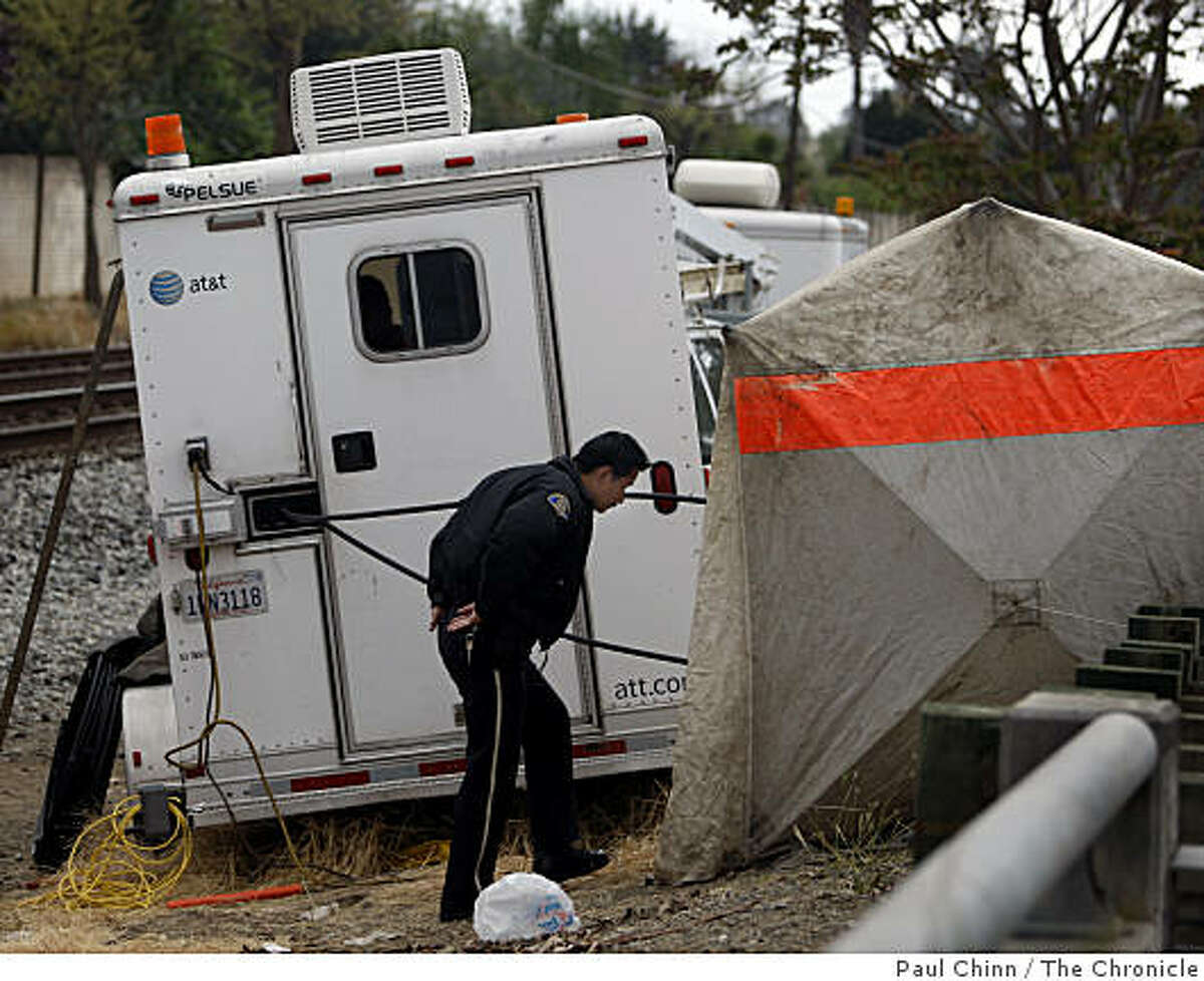 A police officer enters a tent covering the underground vault where fiber-optic communication cables were severed in the early morning hours on Monterey Highway in San Jose on Thursday.