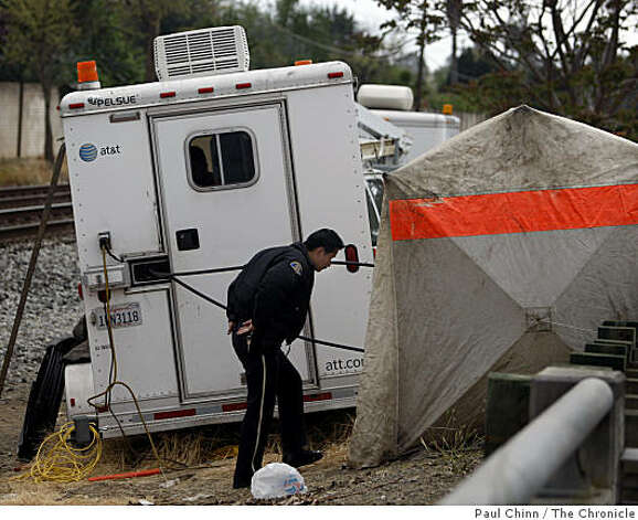 A police officer enters a tent covering the underground vault where fiber-optic communication cables were severed in the early morning hours on Monterey Highway in San Jose on Thursday. Photo: Paul Chinn, The Chronicle