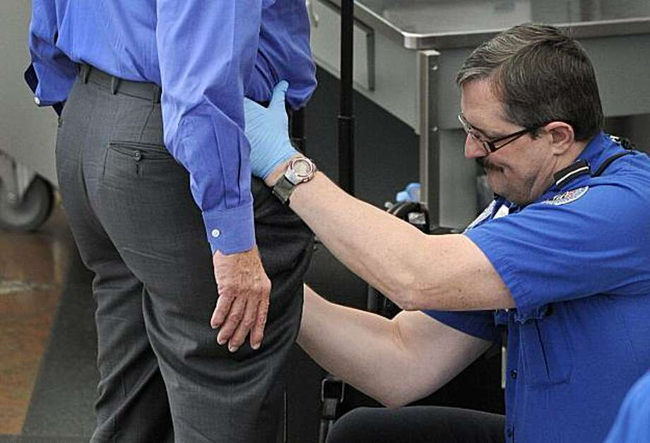In this photo taken on Nov. 17, 2010, a Transportation Security Administration agent performs an enhanced pat-down on a traveler at a security area at Denver International Airport in Denver. (AP Photo/ The Denver Post, Craig F. Walker) DENVER OUT. MAGS OUT.  TV OUT. NO INTERNET. NO SALES Photo: Craig F. Walker, Associated Press