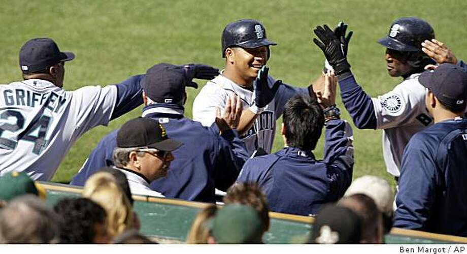 Seattle Mariners' Jose Lopez, center, is welcomed to the dugout after scoring a run against the Oakland Athletics in the eighth inning of a game Saturday, April 11, 2009, in Oakland. Lopez scored on a single by Kenji Johjima. Photo: Ben Margot, AP