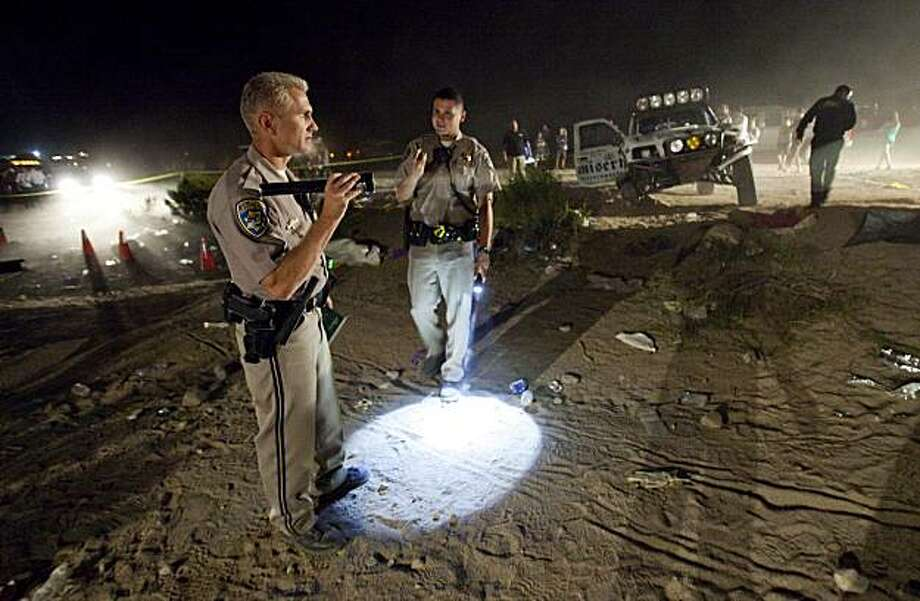 FILE - In this Aug. 15, 2010 file photo, California Highway Patrol officers examine the accident scene Sunday where an off-road race truck went out of control and plowed into a crowd of spectators during a race in Lucerne Valley, Calif. At least eight people were killed and 12 injured during the incident about 100 miles east of Los Angeles.  The U.S Bureau of Land Management says its staff failed to follow established procedures for permitting and monitoring a Mojave Desert off-road race in which eight spectators were killed. An internal review released Friday, Nov. 19, 2010,  found that BLM staff in California did not hold a pre-race consultation with promoters and did not get a detailed operating plan as required. Photo: Francis Specker, AP