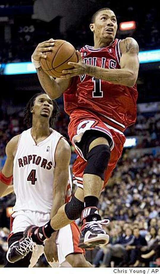 Chicago Bulls' Derrick Rose (1)  drives to the basket as Toronto Raptors' Chris Bosh (4) looks on during the fourth quarter of an NBA basketball game in Toronto on Sunday, March 29, 2009. (AP Photo/The Canadian Press, Chris Young) Photo: Chris Young, AP