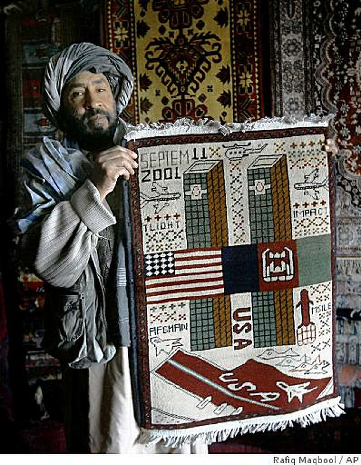"""** ADVANCE FOR SUNDAY, APRIL 12 **Haji Qundi Shah, an Afghan carpet seller displays a war rug which shows the planes attacking the World Trade Center at his shop in Kabul, Afghanistan, Tuesday, Feb 24, 2009. Afghanistan's three decades of fighting and insecurity have spawned a thriving """"war rug"""" business for an international clientele of military buffs and soldiers.(AP Photo/Rafiq Maqbool)"""