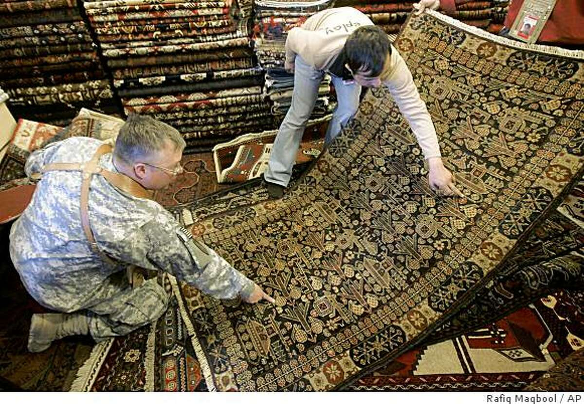 ** ADVANCE FOR SUNDAY, APRIL 12 **Abdullah Ansari, an Afghan carpet seller explains a war rug to U.S Lt. Col. Kevin Holt at Ansari's shop in Camp Eggers, the U.S. base in Kabul, Afghanistan, Thursday, March 12, 2009. Holt says he has spent about $3,000 on 15 war rugs during his Afghanistan deployment.The big money comes from the old Soviet-era carpets he bought, but he's bought plenty of newer productions as well, hoping that they'll gain value. (AP Photo/Rafiq Maqbool)