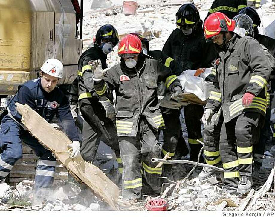 Firefighters carry out a body from the rubble of a collapsed building, in L'Aquila, central Italy, Tuesday, April 7, 2009. Tens of thousands of people left homeless by the powerful magnitude quake slept in makeshift tents that provided little protection against the chilly mountain air. Entire blocks were flattened in the mountain city of L'Aquila and nearby villages by Monday's temblor that killed at least 179 people and injured 1,500. (AP Photo/Gregorio Borgia) Photo: Gregorio Borgia, AP