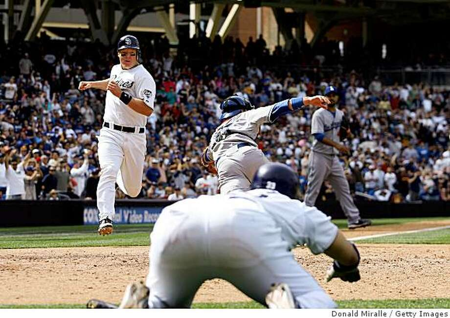 SAN DIEGO, CA - APRIL 9:   Nick Hundley #4 of the San Diego Padres runs in for the go ahead run past the tag of catcher Russell Martin #55 of the Los Angeles Dodgers in the 8th inning on April 9, 2009 at Petco Park in San Diego, California. (Photo by Donald Miralle/Getty Images) Photo: Donald Miralle, Getty Images