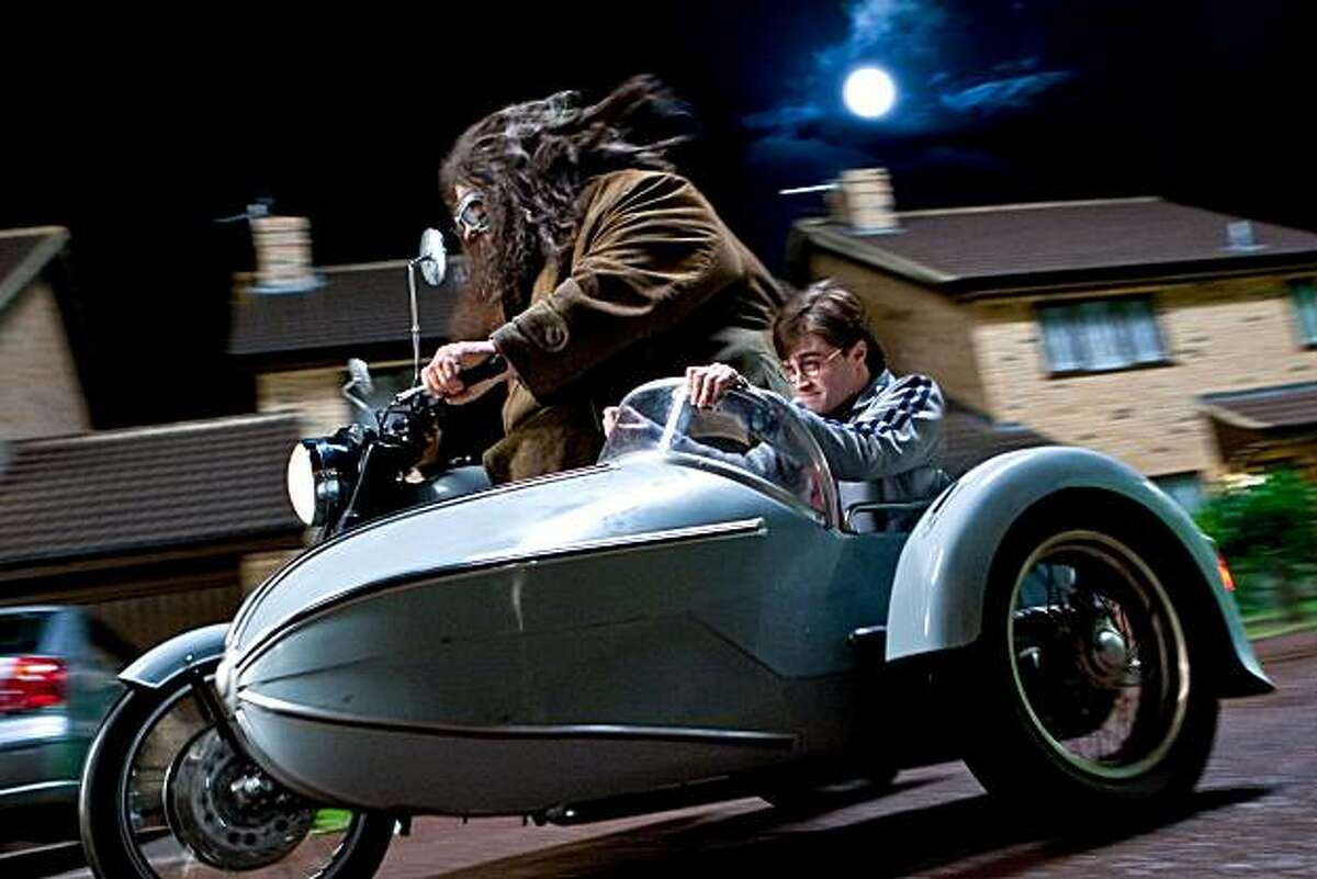 In this film publicity image released by Warner Bros. Pictures, Robbie Coltrane, left, and Daniel Radcliffe are shown in a scene from