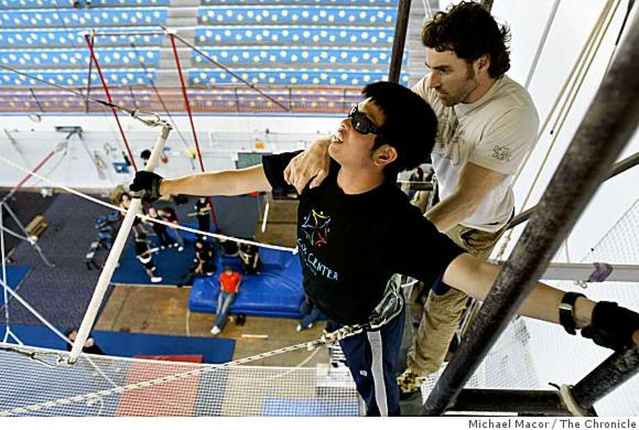 Visually impaired, Chris Young  sets up on overhead platform, with the help from instructor, Jennings McCown,  as he prepares to swing on the trapeze during circus classes at the San Francisco Circus Center  in San Francisco, Calif., on Saturday March 28, 2009. Photo: Michael Macor, The Chronicle