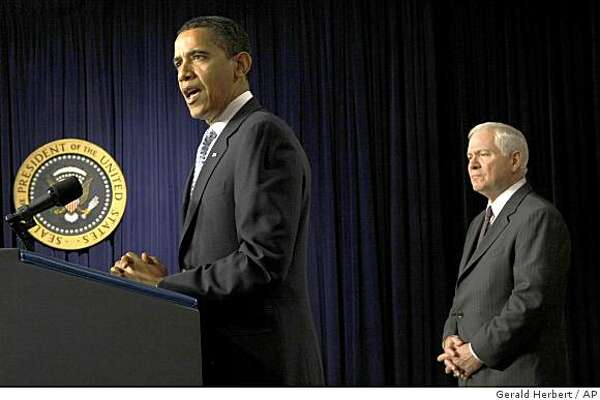 President Barack Obama, accompanied by Defense Secretary Robert Gates, makes remarks on veterans healthcare, Thursday, April 9, 2009, in the Eisenhower Executive Office Building on the White House campus in Washington. (AP Photo/Gerald Herbert)