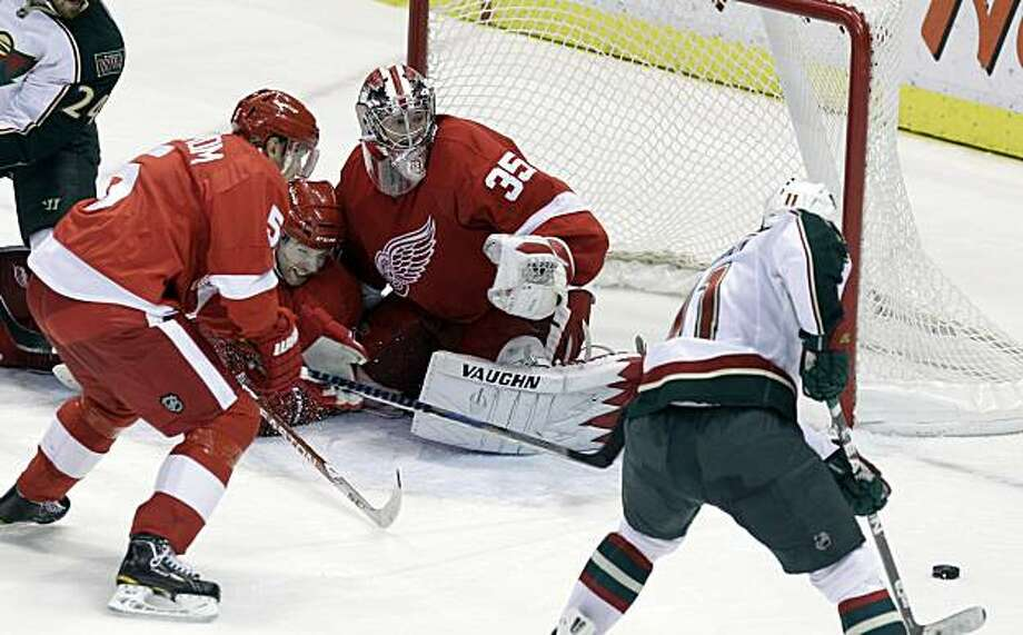 Minnesota Wild center John Madden, right, prepares to shoot the overtime winning goal into the Detroit Red Wings net defended by goalie Jimmy Howard (35), defenseman Brad Stuart, center, and defenseman Nicklas Lidstrom, left, during an NHL hockey game inDetroit, Friday, Nov. 19, 2010. Photo: Carlos Osorio, AP