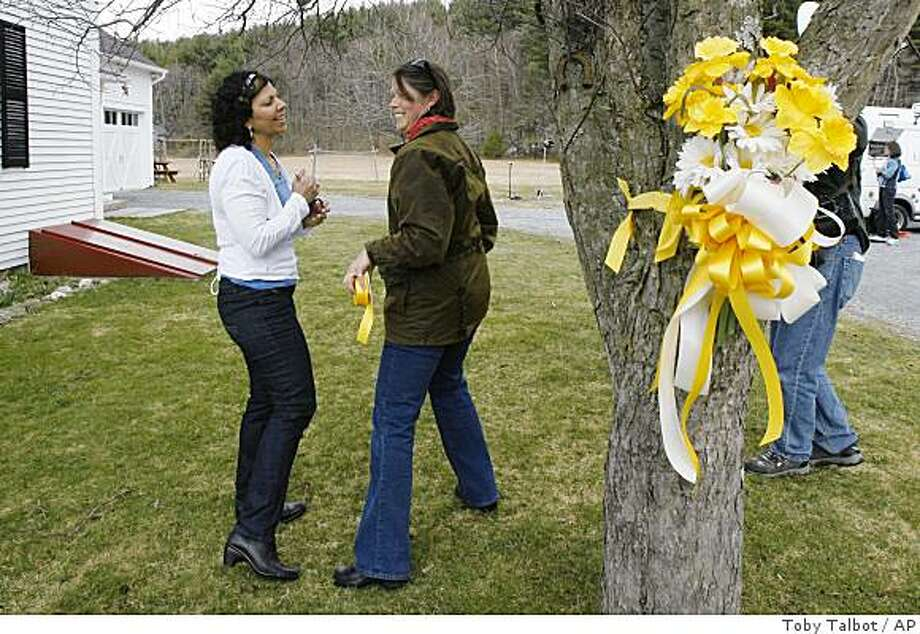 Neighbors of Capt. Richard Phillips talk after hanging a bouquet of yellow flowers on a tree in his front yard in Underhill, Vt., Thursday, April 9, 2009. Phillips is the captain of the  U.S.-flagged cargo ship Maersk Alabama which was hijacked Wednesday by Somali pirates off the Horn of Africa. The captain is held captive on a lifeboat by Somali pirates.  (AP Photo/Toby Talbot) Photo: Toby Talbot, AP
