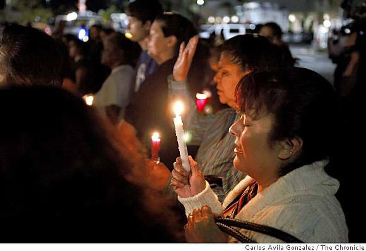 Amelia Orozco, right, and Anita Velasco pray at a candlelight vigil for Sandra Cantu after Tracy authorities held a press conference revealing that the contents of a sealed container that was found earlier in the day were indeed the remains of Sandra Cantu on Monday, April 6, 2009. Cantu has been missing since March 27, 2009.