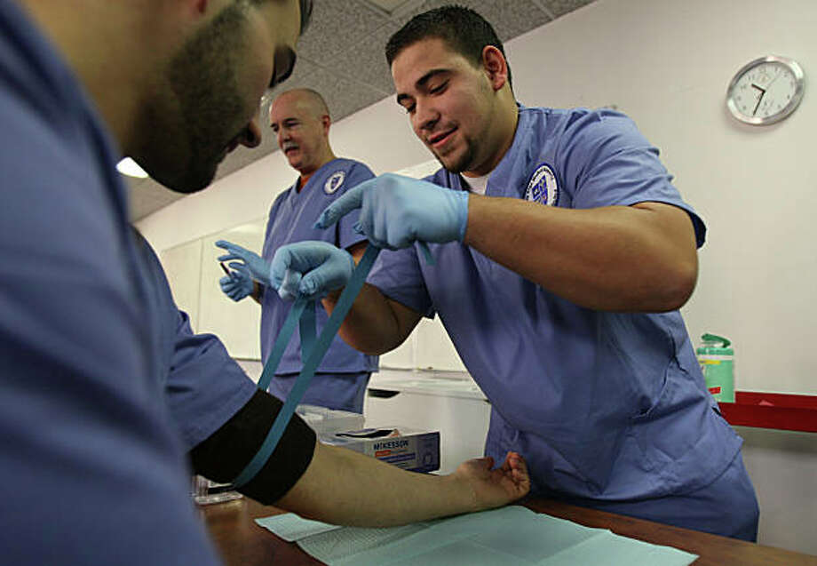 The recession has cut pri? vate sector payrolls in the Bay  Area with one exception —  jobs in the fields of health and  education services increased.   Bay Area Medical Academy students, Amir Hasan, (left), Jeff Bledsoe, (center) and Giovanni Fratangeli, (right) are enrolled in the phlebotomy course. Bledsoe retired from a job in the silicon valley and is now heading into the health care industry, while Fratangeli was just laid off from his job and is now retraining into another profession. Students practice the procedure of drawing blood at the Bay Area Medical Academy on Friday Jan. 16, 2009, in San Francisco, Calif. Photo: Michael Macor, The Chronicle / SFC