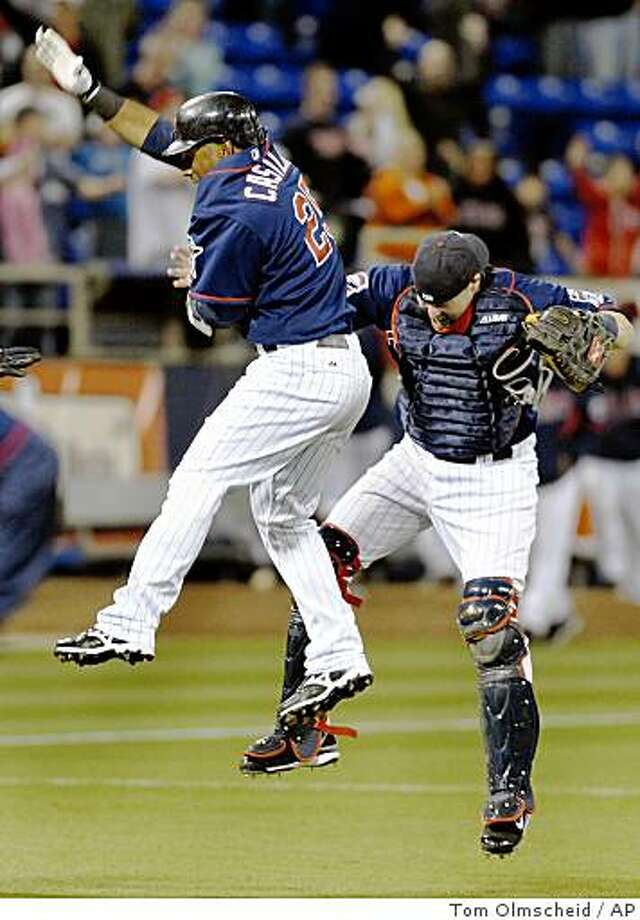 Minnesota Twins' Alexi Casilla, left, celebrates with bullpen catcher Mike Redmond after Casilla singled in two runs in the ninth inning to give the Twins a 6-5 win over the Seattle Mariners in a baseball game Tuesday, April 7, 2009, in Minneapolis. (AP Photo/Tom Olmscheid) Photo: Tom Olmscheid, AP