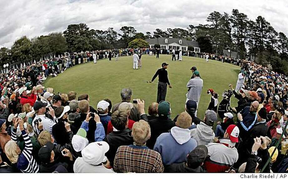 Patrons watch as Tiger Woods practices on the putting green in preparation for the Masters golf tournament at the Augusta National Golf Club in Augusta, Ga., Tuesday, April 7, 2009. (AP Photo/Charlie Riedel) Photo: Charlie Riedel, AP
