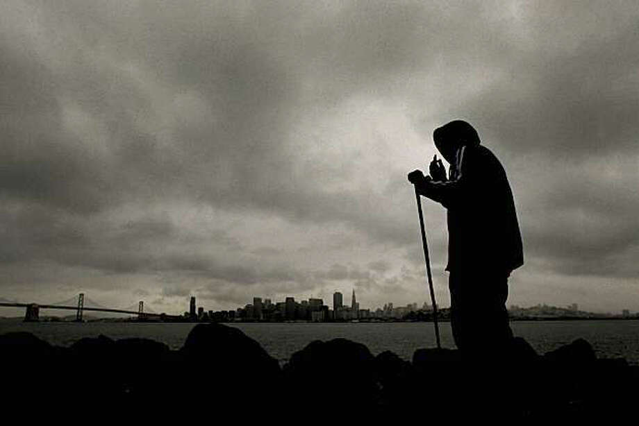 David Coler looks out over San Francisco Bay from Treasure Island in as an approaching weather front inches closer to the Bay Area on Friday. Photo: Michael Macor, The Chronicle