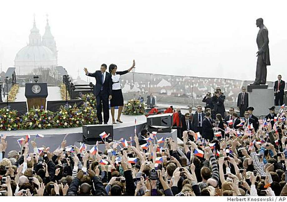 US President Barack Obama, left, and his wife Michelle greet the crowd prior to his speech in front of the Castle in Prague, Czech Republic, Sunday, April 5, 2009. Obama will also attend a summit between the United States and the 27-member European Union in Prague on Sunday. Seen in background left is the St. Nicholas church, on right is the statue of of Tomas Garrigue Masaryk, the first President of former Czechoslovakia.  (AP Photo/Herbert Knosowski) Photo: Herbert Knosowski, AP