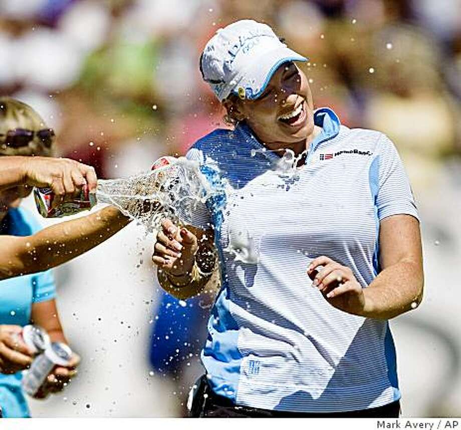 Brittany Lincicome gets sprayed with beer after sinking an eagle putt on the 18th hole to win the LPGA Kraft Nabisco Championship golf tournament in Rancho Mirage, Calif., Sunday, April 5, 2009.  (AP Photo/Mark Avery) Photo: Mark Avery, AP