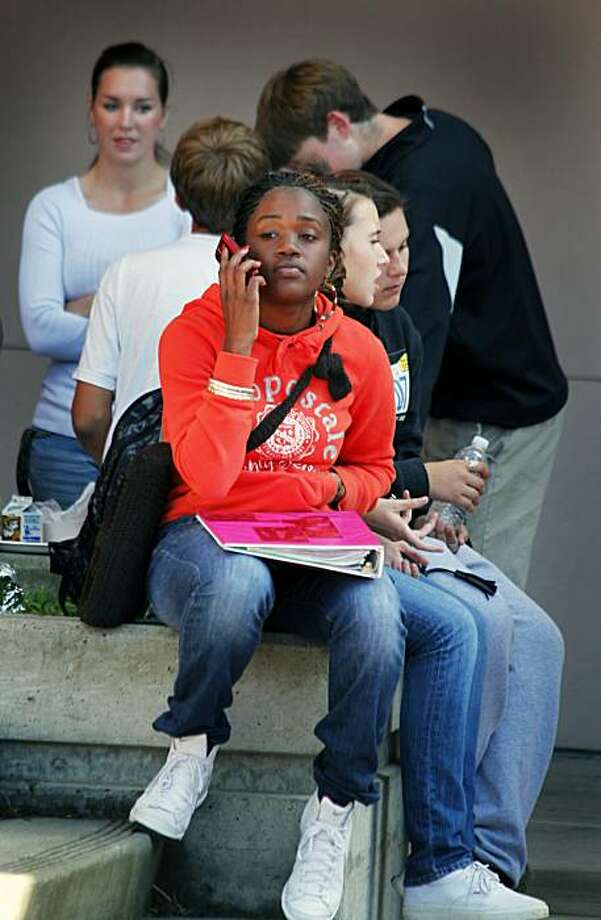 Shaylia Cooper age 15 a freshman at Benicia High School checks her messages during lunch period. Benicia High implemented a new cell phone policy Monday that includes harsh if not draconian punishment, including confiscating the phone for a first offense, requiring students to pick it up on Friday with a parent present. Wednesday Nov. 10, 2010 Photo: Lance Iversen, San Francisco Chronicle