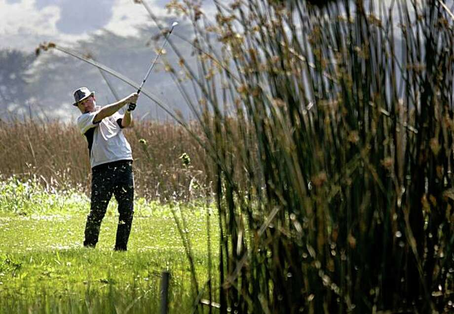 Jamie Kahn hits his golf ball over a marshy hazard to the 15th green at Sharp Park Golf Course in Pacifica, Calif., on Wednesday, April 1, 2009. San Francisco city officials, who own and operate the course, may consider closing the popular 18-hole course to restore the area to its natural wetlands habitat. Photo: Paul Chinn, The Chronicle