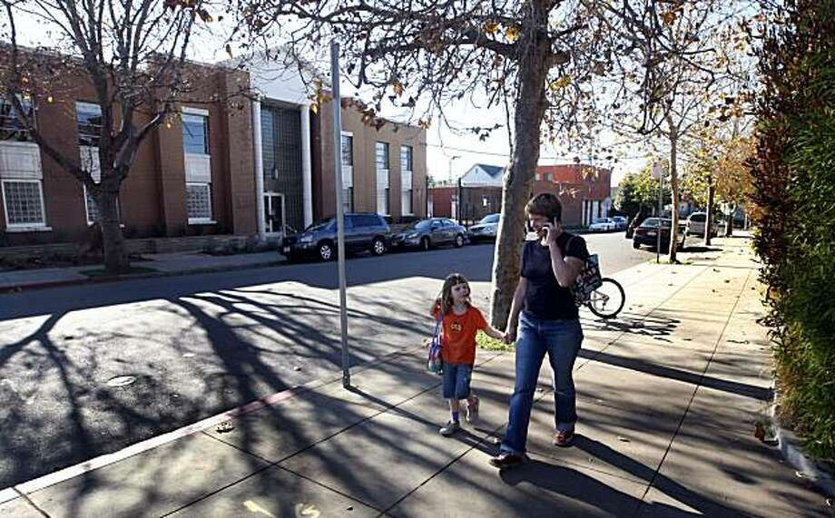 Julia Dwyer picks up her 5-year-old daughter Ella Thompson from North Oakland Community Charter School on 42nd Street on Tuesday. Parents of students are organizing to stop construction of a cellular tower on top of an office building owned by Verizon. Photo: Lance Iversen, The Chronicle