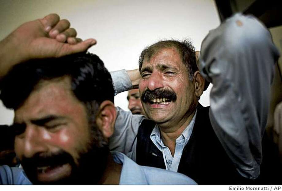 Relatives of victims killed by a suicide bomber in a mosque, react in a hospital in Chakwal city in Punjab province, about 50 miles (80 kilometers) south of Islamabad, Pakistan, Sunday, April 5, 2009. A suicide bomber attacked a crowded Shiite mosque south of the Pakistani capital on Sunday, killing 22 people and wounding dozens more, officials said. (AP Photo/Emilio Morenatti) Photo: Emilio Morenatti, AP
