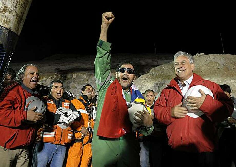 In this file photo released by the Chilean Presidential Press Office Wednesday, Oct. 13, 2010, the last miner to be rescued, Luis Urzua, center, gestures as Chile's President Sebastian Pinera, right, looks on after his rescue from the collapsed SanJose gold and copper mine where he had been trapped with 32 other miners for over two months near Copiapo, Chile. The 33 Chilean miners who captured the worlds imagination for surviving 69 days in a collapsed mine have accepted an Israeli invitation to visit the Holy Land for Christmas. Israeli foreign ministry spokesman Yigal Palmor said Tuesday, Nov. 9, 2010 that the miners had accepted the invitation. Photo: Alex Ibanez, AP