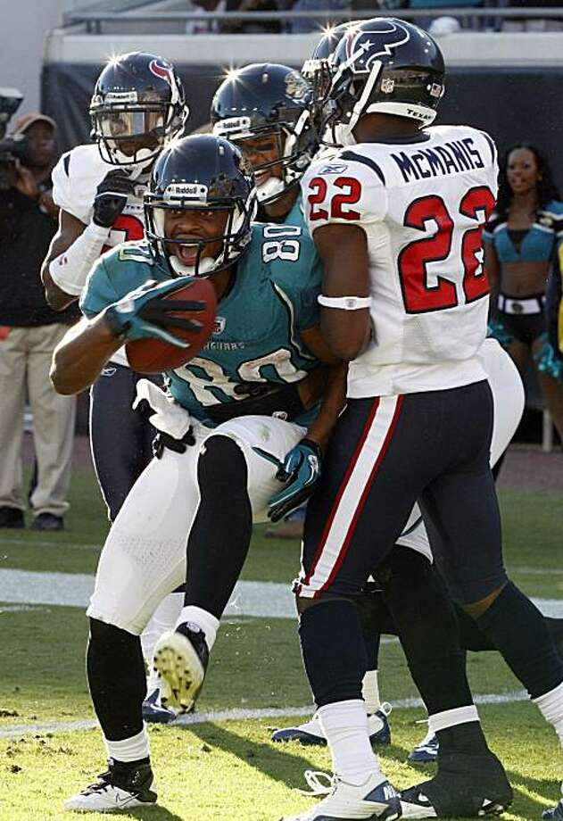 Jacksonville Jaguars wide receiver Mike Thomas (80) catches a 50-yard touchdown pass in front of Houston Texans cornerback Sherrick McManis (22) as time expired on the clock to give Jacksonville a 31-24 victory in an NFL football game in Jacksonville, Fla., Sunday, Nov. 14, 2010. Photo: Reinhold Matay, AP