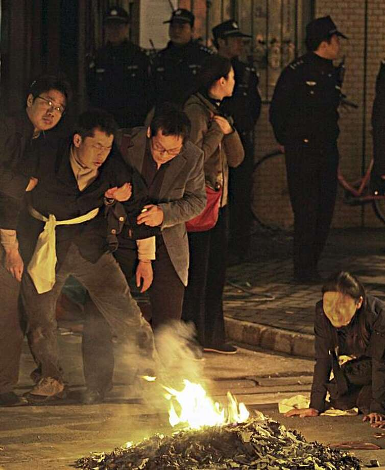 Chinese police officers stand watch the relatives mourn for victims who has killed in the Monday fire on an apartment building in Shanghai, China Tuesday Nov. 16, 2010. Police detained unlicensed welders Tuesday for accidentally starting a fire that engulfed the high-rise apartment building under renovation in China's business capital that killed at least 53 as public anger grew over the government's handling of the disaster. Photo: AP