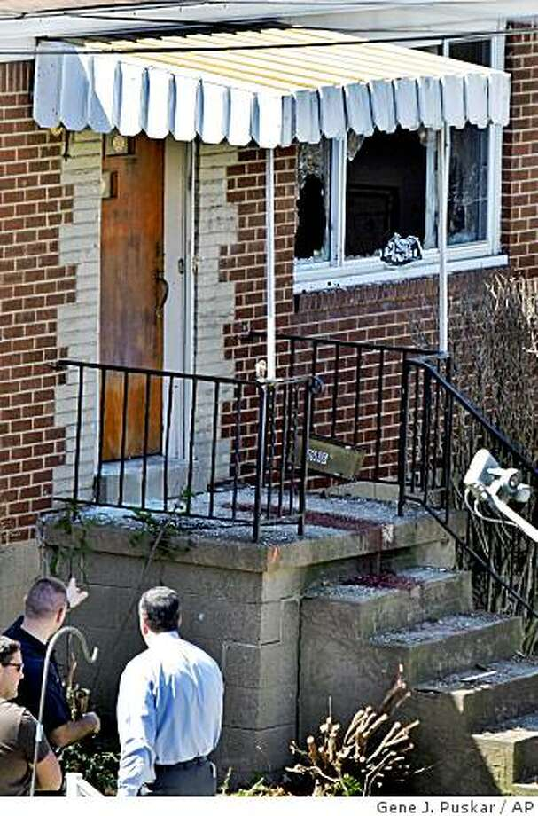 Pittsburgh Police investigators, lower left, look at the blood-stained front steps of 1016 Fairfield street in the Stanton Heights section of Pittsburgh Sunday, April 5, 2009. 23-year-old Richard Poplawski, according to court papers, opened fire on Pittsburgh police officers responding to a 911 call from the gunman's mother, killing three officers. (AP Photo/Gene J. Puskar) Photo: Gene J. Puskar, AP