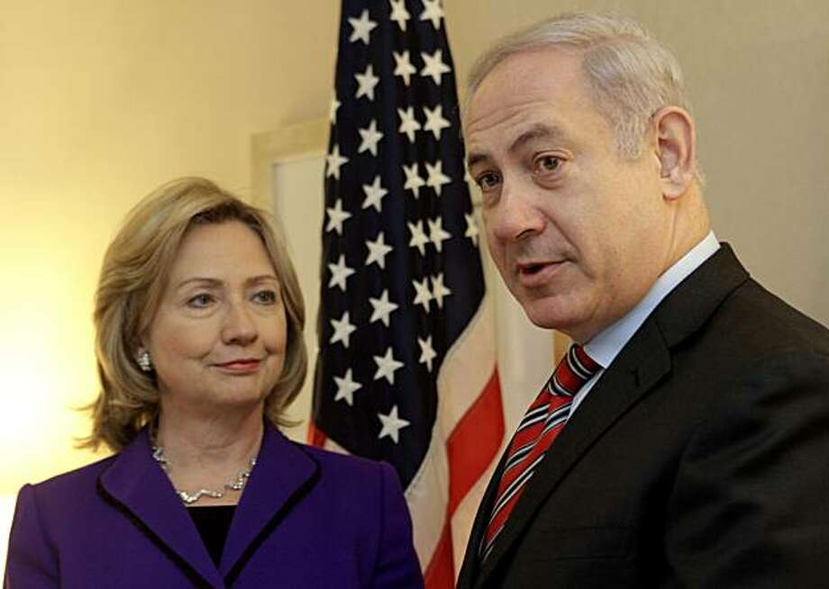U.S. Secretary of State Hillary Rodham Clinton, left, listens as Israeli Prime Minister Benjamin Netanyahu speaks to reporters during a meeting in New York, Thursday, Nov. 11, 2010. Photo: Mary Altaffer, AP