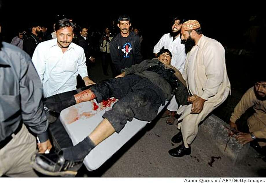 Pakistani security personnel use a stretcher to carry an injured colleague, victim of a suicide blast, at a security force checkpoint in Islamabad on April 4, 2009. Six people were killed in an apparent suicide attack near the checkpoint in the Pakistani capital Islamabad, a police official told reporters.    TOPSHOTS/AFP PHOTO/ Aamir QURESHI (Photo credit should read AAMIR QURESHI/AFP/Getty Images) Photo: Aamir Qureshi, AFP/Getty Images