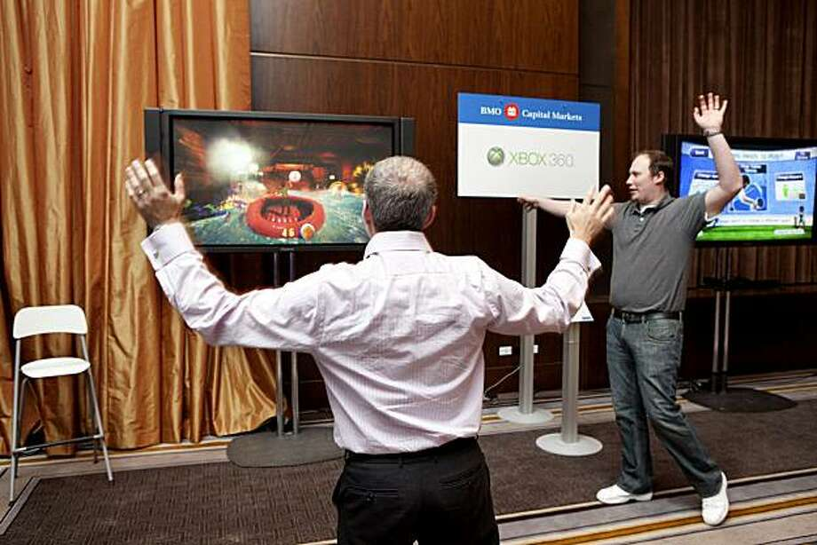 """Daniel Googel, left, plays the Kinect Adventures game on Microsoft Corp.'s Xbox 360 console at the BMO Capital Markets Annual Digital Entertainment Conference in New York, U.S., on Thursday, Nov. 11, 2010. Blockbuster video games, like Acitivsion Blizzard Inc.'s """"Call of Duty: Black Ops,"""" which posted a record $360 million in sales in North America and the U.K. in 24 hours, have eclipsed movies and other forms of entertainment in sales. Photographer: JB Reed/Bloomberg Photo: JB Reed, Bloomberg"""