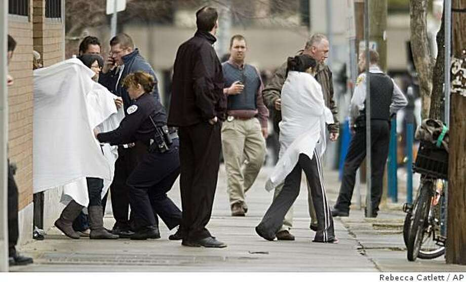 Hostages exit a building near the American Civic Association in downtown Binghamton, N.Y., following a shooting spree by a gunman Friday April 3, 2009. A law enforcement official says the gunman who killed at least 12 people in Binghamton, N.Y., died of a self-inflicted gunshot wound. (AP Photo/Press & Sun-Bulletin, Rebecca Catlett) Photo: Rebecca Catlett, AP